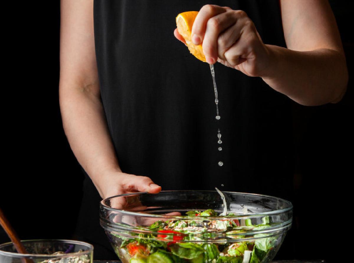 come spremi i limoni probabilmente woman squeezing lemon into chunky salad side view 176474 5547